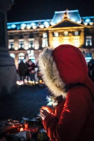 Photo for Large crowd of people mourners gathered near General Kleber statue to attend a vigil with multiple light candles flowers and messages for the victims of terrorist Cherif Chekatt at Christmas Market. - Royalty Free Image