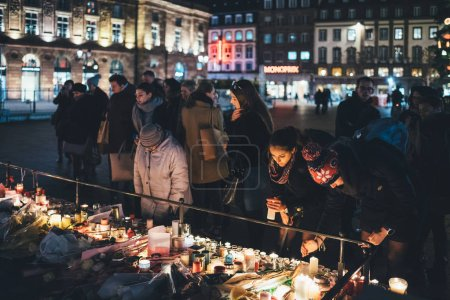 Photo for STRASBOURG, FRANCE - DEC 13, 2018: Large crowd of people mourners gathered near General Kleber statue to attend a vigil with multiple lighting candles flowers and messages for the victims of terrorist - Royalty Free Image