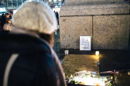 Photo for STRASBOURG, FRANCE - DEC 13, 2018: Woman looking at icon with Strasbourg Cathedral crying at General Kleber statue to attend a vigil with multiple light candles flowers and messages for the victims of - Royalty Free Image