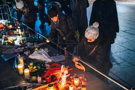 Photo for STRASBOURG, FRANCE - DEC 13, 2018: Women friends lighting candles at General Kleber statue at the vigil with multiple light candles flowers and messages for the victims of terrorist Cherif Chekatt at - Royalty Free Image