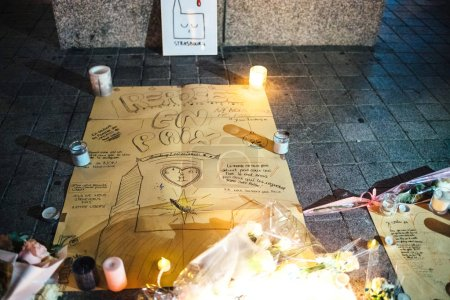 Photo for STRASBOURG, FRANCE - DEC 13, 2018: Rest in Peace mesage in French at the base of General Kleber statue vigil with multiple light candles flowers and messages for the victims of terrorist Cherif - Royalty Free Image