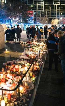 Photo for STRASBOURG, FRANCE - DEC 13, 2018: Side view of people mourners near General Kleber statue to attend a vigil with lighting multiple light candles flowers and messages for the victims of terrorist - Royalty Free Image