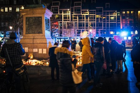 Photo for STRASBOURG, FRANCE - DEC 13, 2018: Visitors and locals people mourners gathered near General Kleber statue to attend a vigil with multiple light candles flowers and messages for the victims of - Royalty Free Image