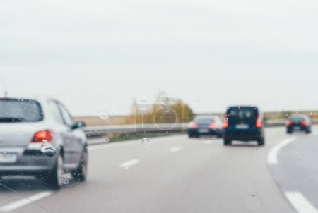 Photo for Defocused view of cars on german highway autobahn on a rainy day focus on water drops on windshield - Royalty Free Image