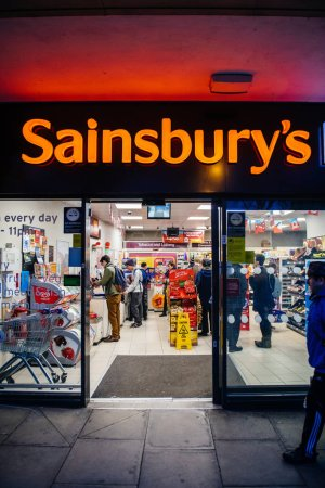 Photo pour Oxford, Royaume-Uni - 3 mars 2017: Magdalen St, Oxford Ox1 3ad with Sainsburys Local supermarket at stsk main entrance with customers inside view from the street - image libre de droit