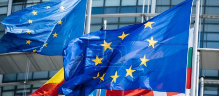Photo for Detail of flags of all member states of the European Union waving in calm wind in front of the Parliament headquarter on the day of 2019 European Parliament election. - Royalty Free Image