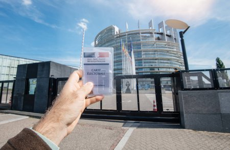 Photo for Strasbourg, France - May 26, 2019: man hand holding Voter's car French Carte Electorale at the entrance of European Parliament headquarter building with all flags on the 2019 European Parliament election day - Royalty Free Image