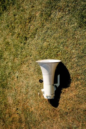 Photo for Green digital megaphone left on the green vivid grass during social protest - Royalty Free Image