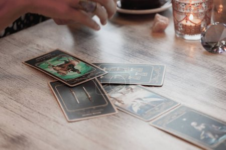 Photo for Woman is reading Tarot cards on the table in cafe - Royalty Free Image
