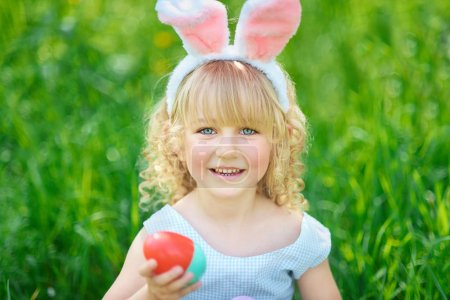 Photo for Cute funny girl with Easter eggs and bunny ears at garden. Easter concept. Laughing child at Easter egg hunt. Child in park with basket full of eggs, spring concept - Royalty Free Image