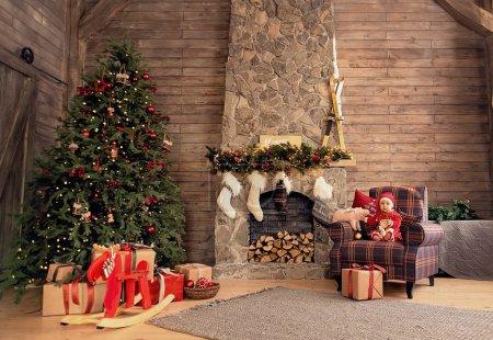 Photo pour La petite fille sous le sapin de Noël. bébé fille dans le chapeau du Père Noël avec des cadeaux sous l'arbre de Noël à la cheminée avec jouet cochon - image libre de droit