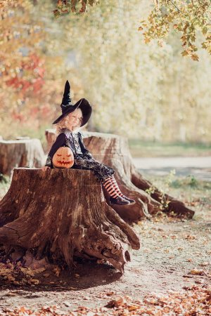 Photo for Beautiful girl witch. little girl in witch costume celebrate Halloween outdoor and have fun. Kids trick or treating - Royalty Free Image