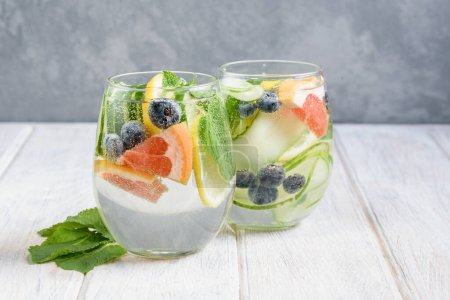 Photo for Summer drink with lemon, mint, cucumber, blueberry and grapefruit. Lemonade refreshing and detox. Healthy eating concept. Light background. Close-up. Body detoxication. - Royalty Free Image