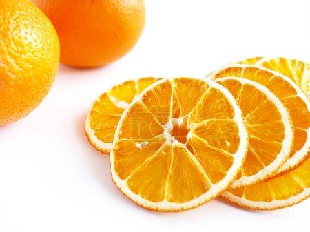 Photo pour Oranges entières fraîches et tranches d'orange séchées sur surface blanche - image libre de droit