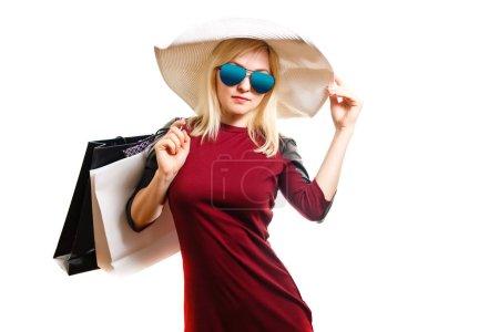 Photo pour Femme en robe rouge tenant des sacs à provisions isolés sur blanc - image libre de droit