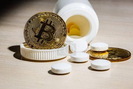 Bitcoin and pills on light background
