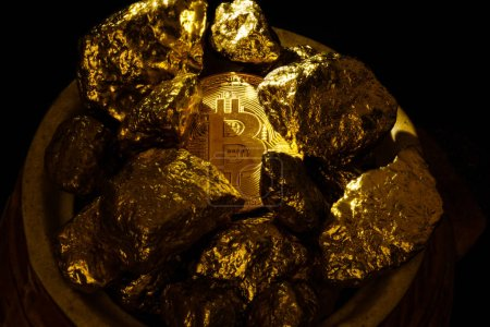 Closeup of big gold nugget and gold bitcoins coins on black background bitcoin cryptocurrency