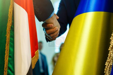 Handshake between ukraine and united arab emirates flags