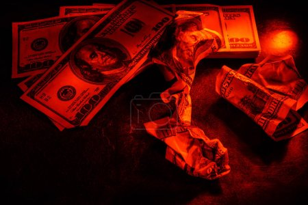 Three crumpled dollar bills on dark background