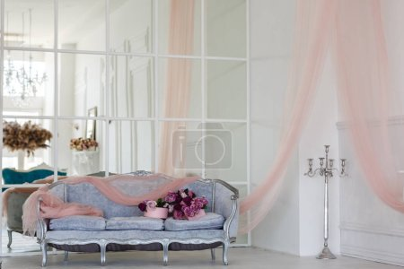 Photo for Vintage style sofa decorated with flowers in loft interior room with big window. - Royalty Free Image