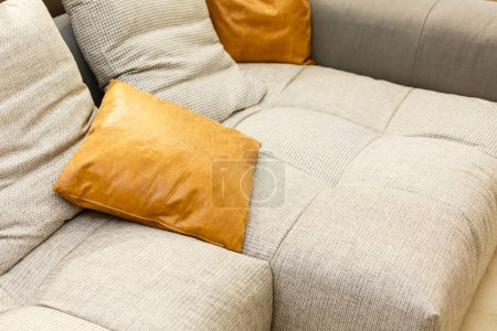 White leather sofa with orange pillow