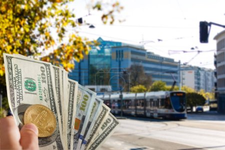 Photo for Golden bitcoin and dollars in hand on background of bus - Royalty Free Image