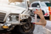 Woman using mobile smartphone take car crash accident for insurance