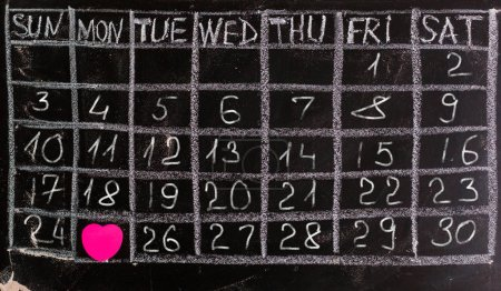 Freehand white chalk doodle sketch of blank monthly grid timetable schedule on black chalkboard