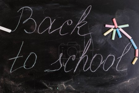 Colorful wallpaper pattern with colored chalks on blackboard back to school concept background