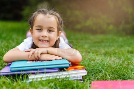 little girl lies on the grass with a book in the park