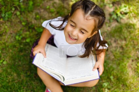 Photo pour Portrait en plein air d'une adorable petite fille lisant un livre dans le jardin - image libre de droit
