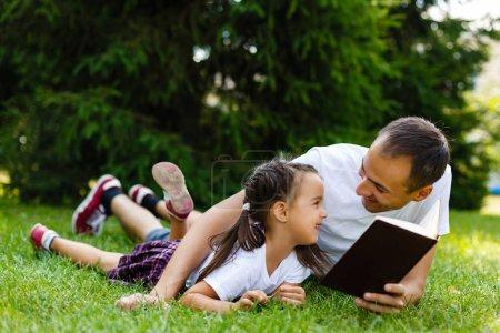 Photo pour Jeune père avec sa petite fille lecture livre couché sur l'herbe verte - image libre de droit