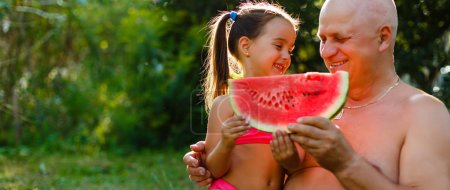 Grandfather and granddaughter eating watermelon and laughing sitting on green grass in garden