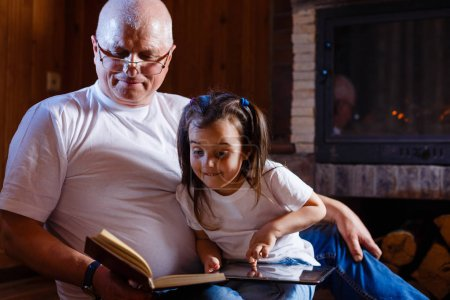 grandfather with book and grandchild with smartphone sitting at home near the fireplace