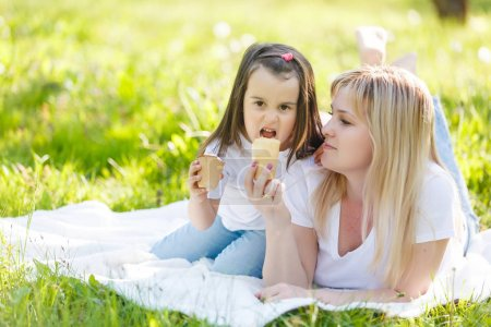 Photo for Happy mom and daughter. Walk in the green park Mother and little daughter ice cream nature - Royalty Free Image