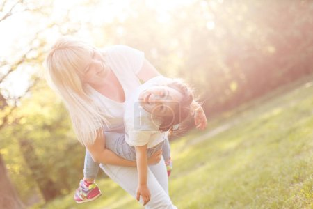 Young mom and cheerful adorable girl having fun together in park in summertime