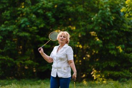senior woman holding badminton racket standing in green park