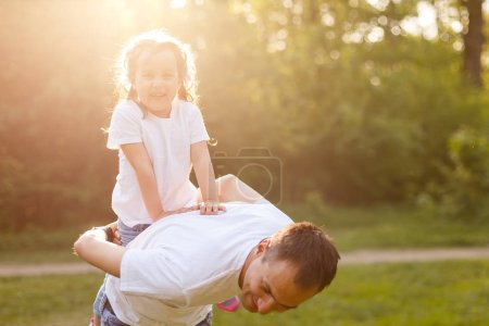 young man is playing with his daughter in the nature. The father is standing and carrying girl on his back. He is stretching arms sideways. happy family having fun outdoors Happy family playing in nature