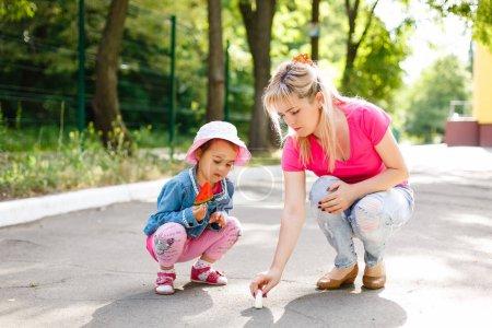 Photo pour Mère enseignant à sa fille mignonne à dessiner à la craie sur le trottoir - image libre de droit