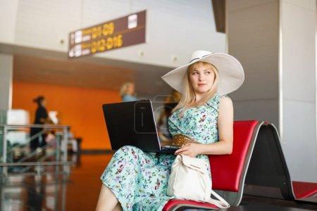 Photo pour Jeune passagère à l'aéroport, utilisant sa tablette en attendant son vol - image libre de droit