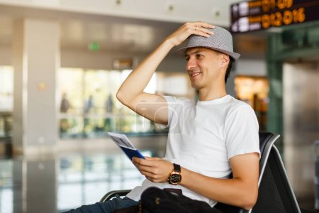 Photo for Man wearing hat holding passport and boarding pass at airport - Royalty Free Image