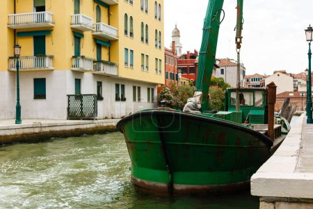 Red and Green tank boat docked in Canal, Venice, Italy.