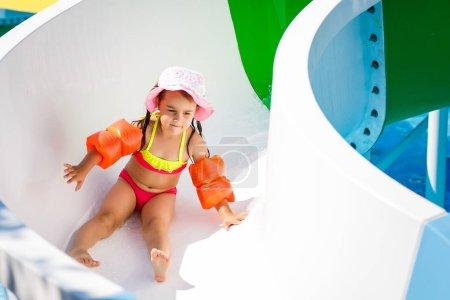 happy little girl sliding down on water slide in aqua park