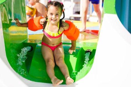 little girl sliding down on water slide at aqua park