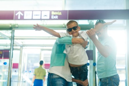 Young family with son having fun in airport before departure