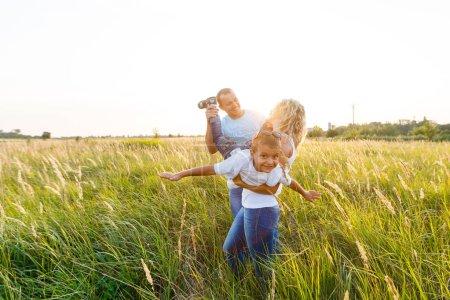Photo pour Jeune famille avec fils marche et passer de bon moment dans le domaine en vert au coucher du soleil - image libre de droit