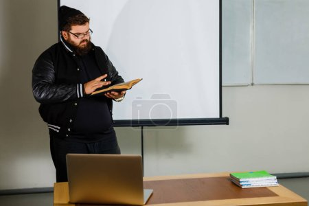 male teacher reading book standing in class room