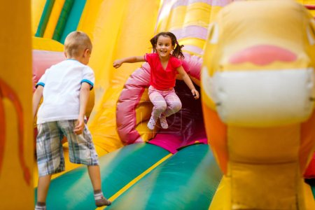 Photo for Joyful little girl playing on a trampoline. - Royalty Free Image