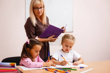Photo for Young preschool teacher teaching little girls in classroom - Royalty Free Image