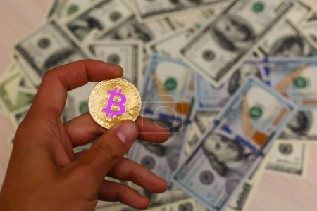 Golden bitcoin coin on male hand on blurred us dollar bills background copy space